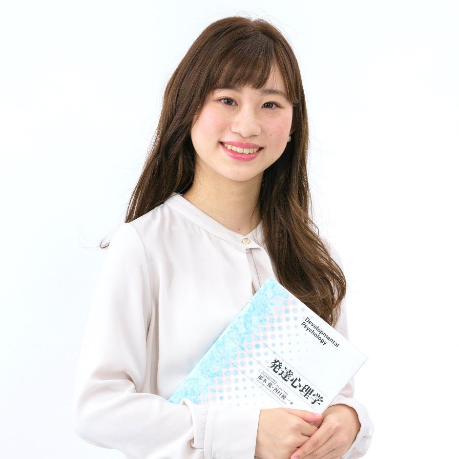 画像:テキストを抱える笑顔の学生
